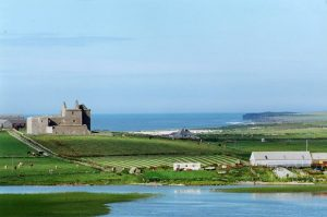 Noltland Castle with the North Atlantic in the distance and Burness Loch in the foreground